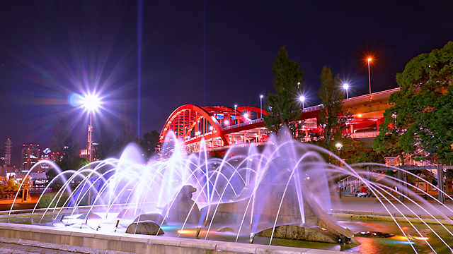 イルカの彫刻のある噴水と神戸大橋の夜景